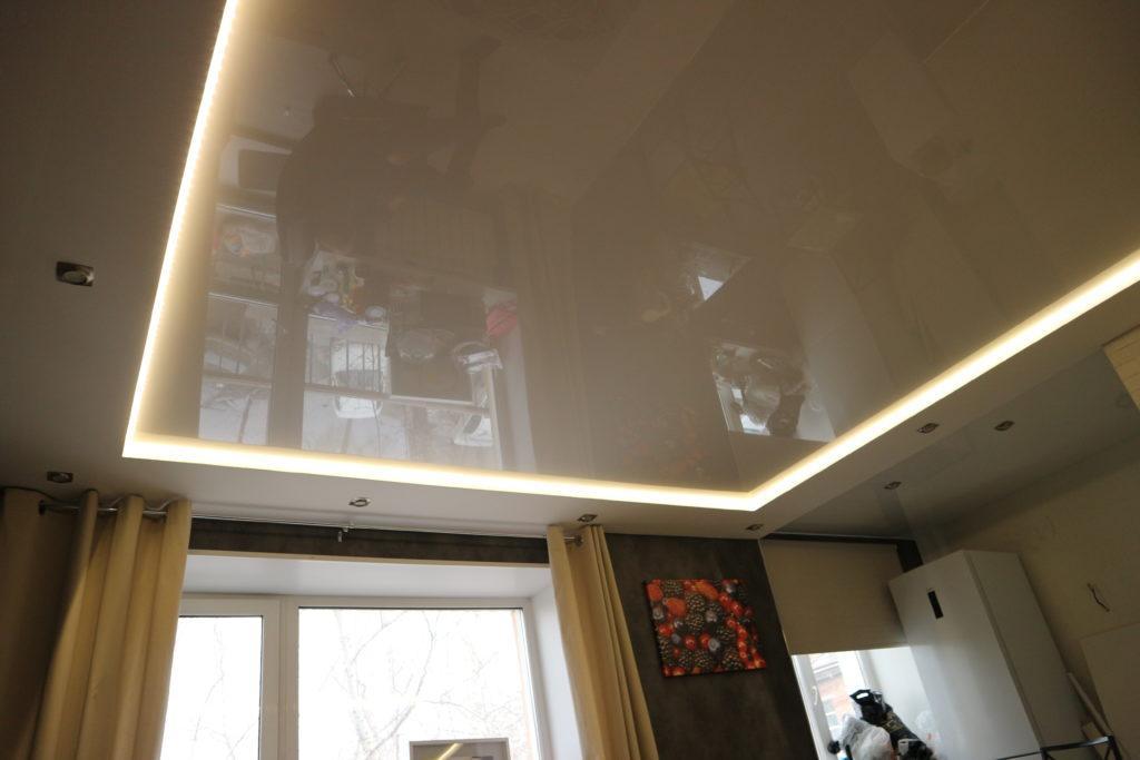 Бежевый глянцевый натяжной потолок с подсветкой в зал